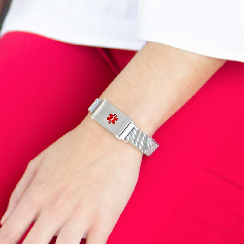 Woman wearing the silver-tone stainless Urban Medical Alert bracelet with mesh chain and affixed ID tag with red caduceus