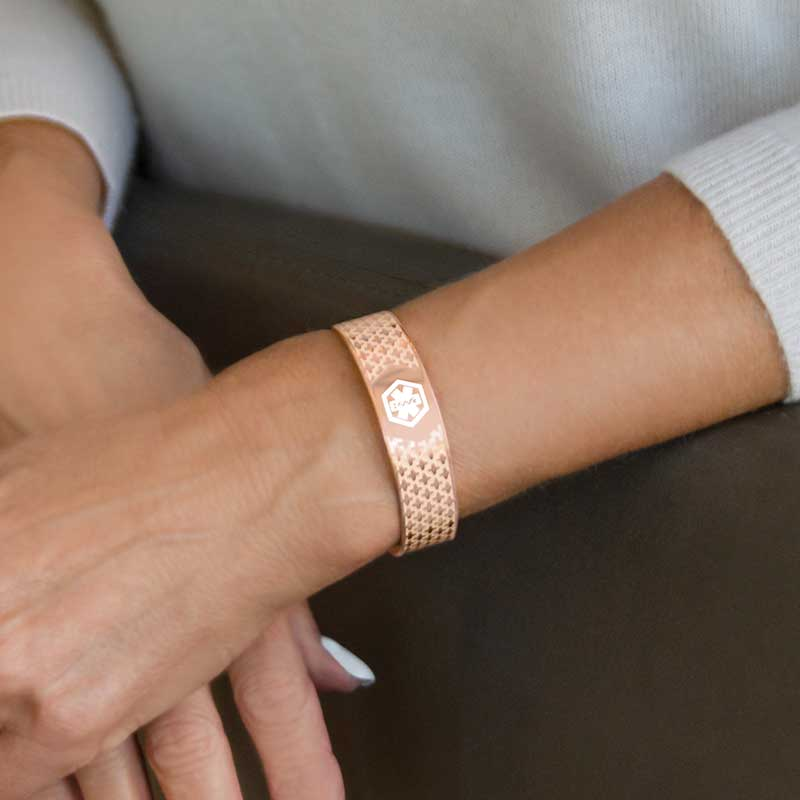 Woman showing the front of rose gold medical ID cuff with white medical symbol / --