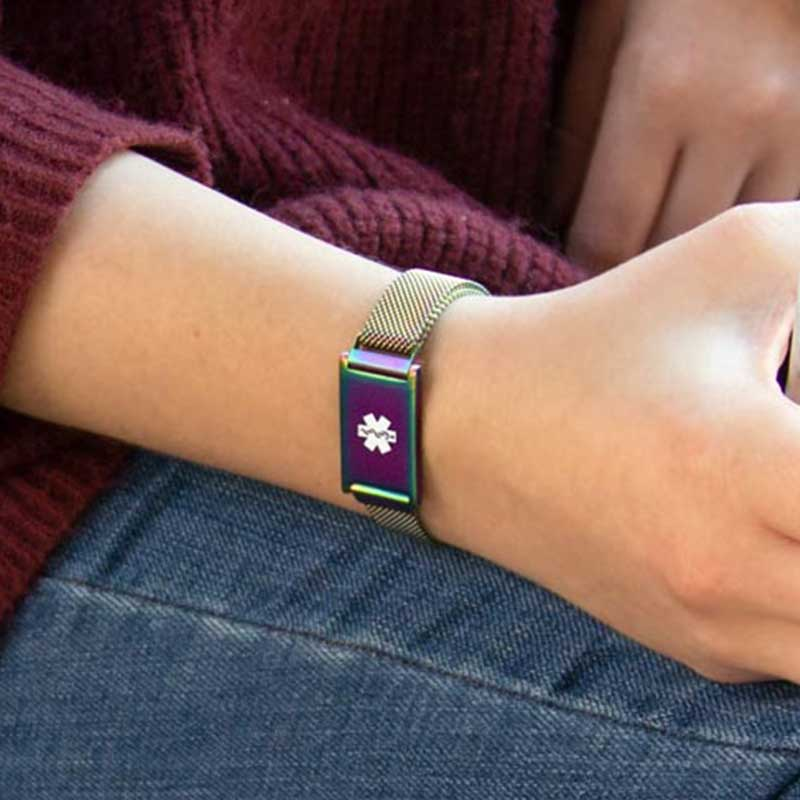 Woman holding a drink wearing adjustable medical ID bracelet with magnetic closure in oil slick, color changing finish and mesh band