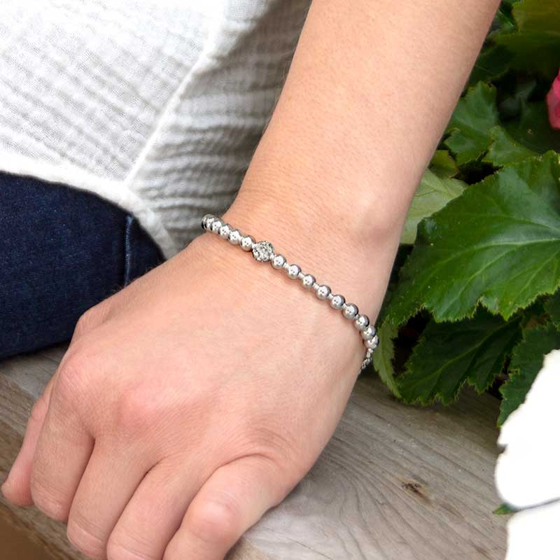 Woman wearing B654 - Olivia Stretch Bracelet with silver beads in flowers