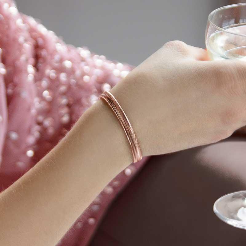 Woman wearing rose gold herringbone medical ID bracelet and holding drink