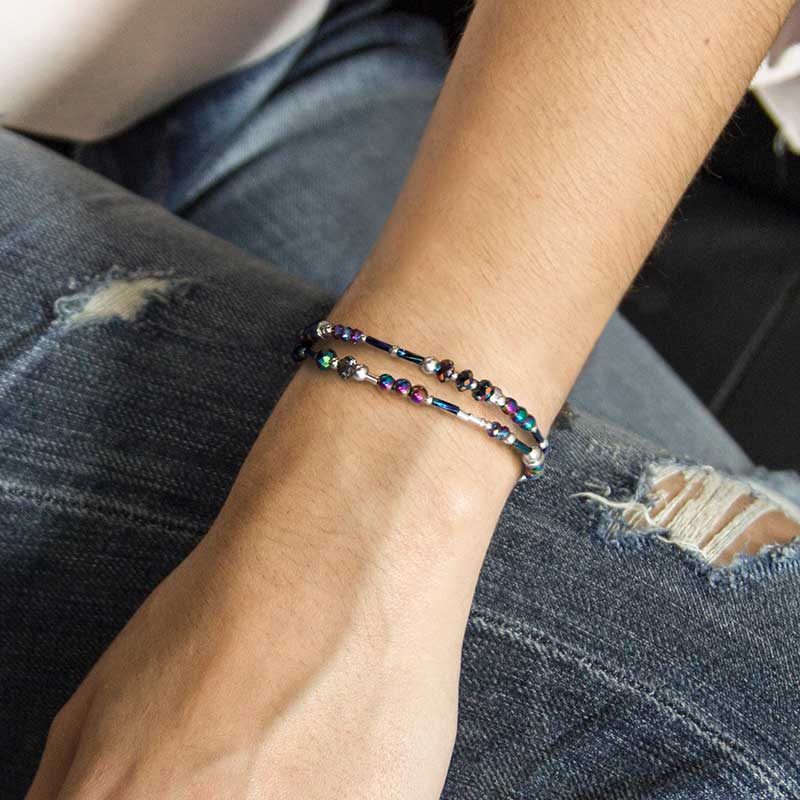 Woman wearing beaded blue and purple medical ID bracelet with silver accents