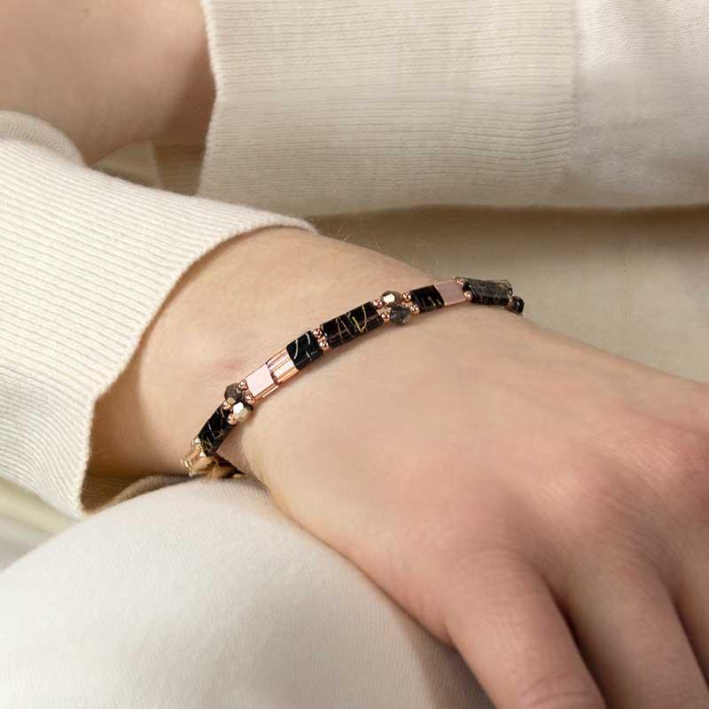 Woman wearing black and rose gold stretch medical alert beaded bracelet