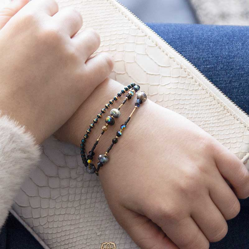 Woman wearing beaded medical alert bracelet with gold accents