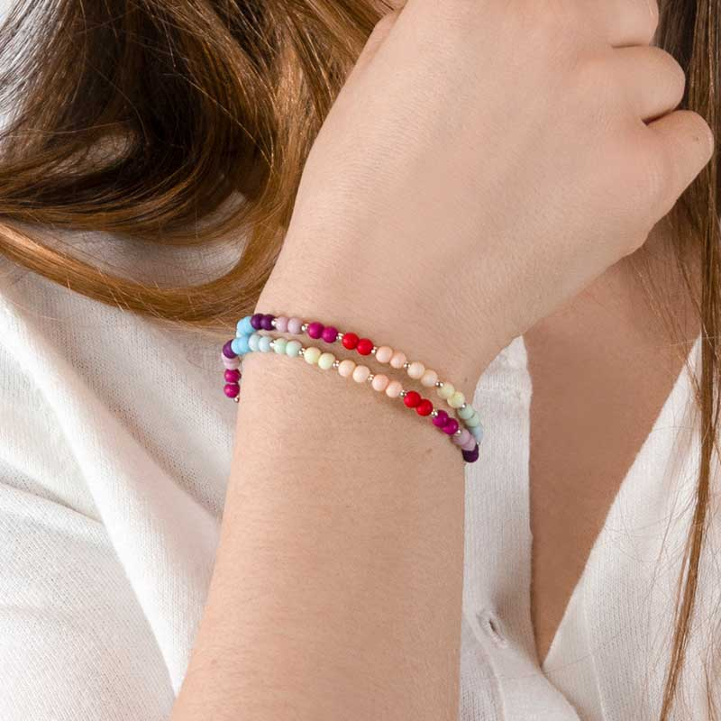 Woman wearing multicolor medical alert bracelet with colorful beaded components